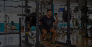 man squatting with trainer helping
